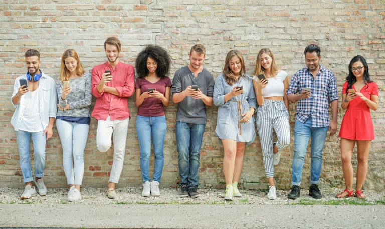 Group of young people standing against a wall using their smartphones