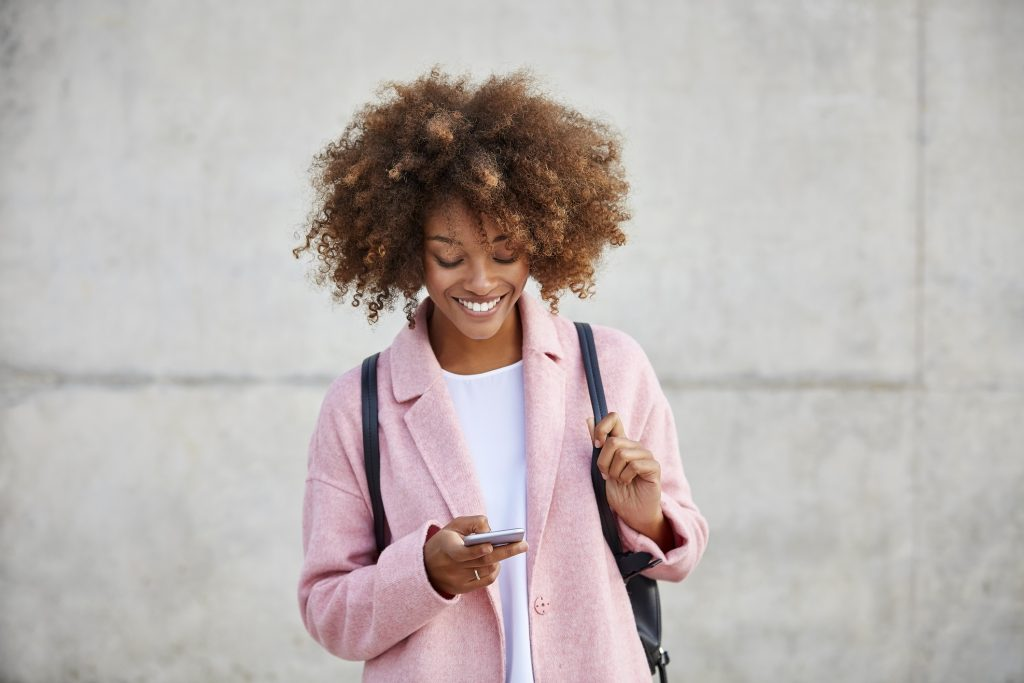 Young woman in a pink coat using a smartphone