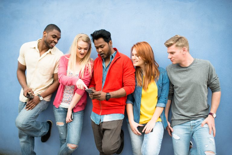 Group of young people gathered at a wall looking at their friend's phone